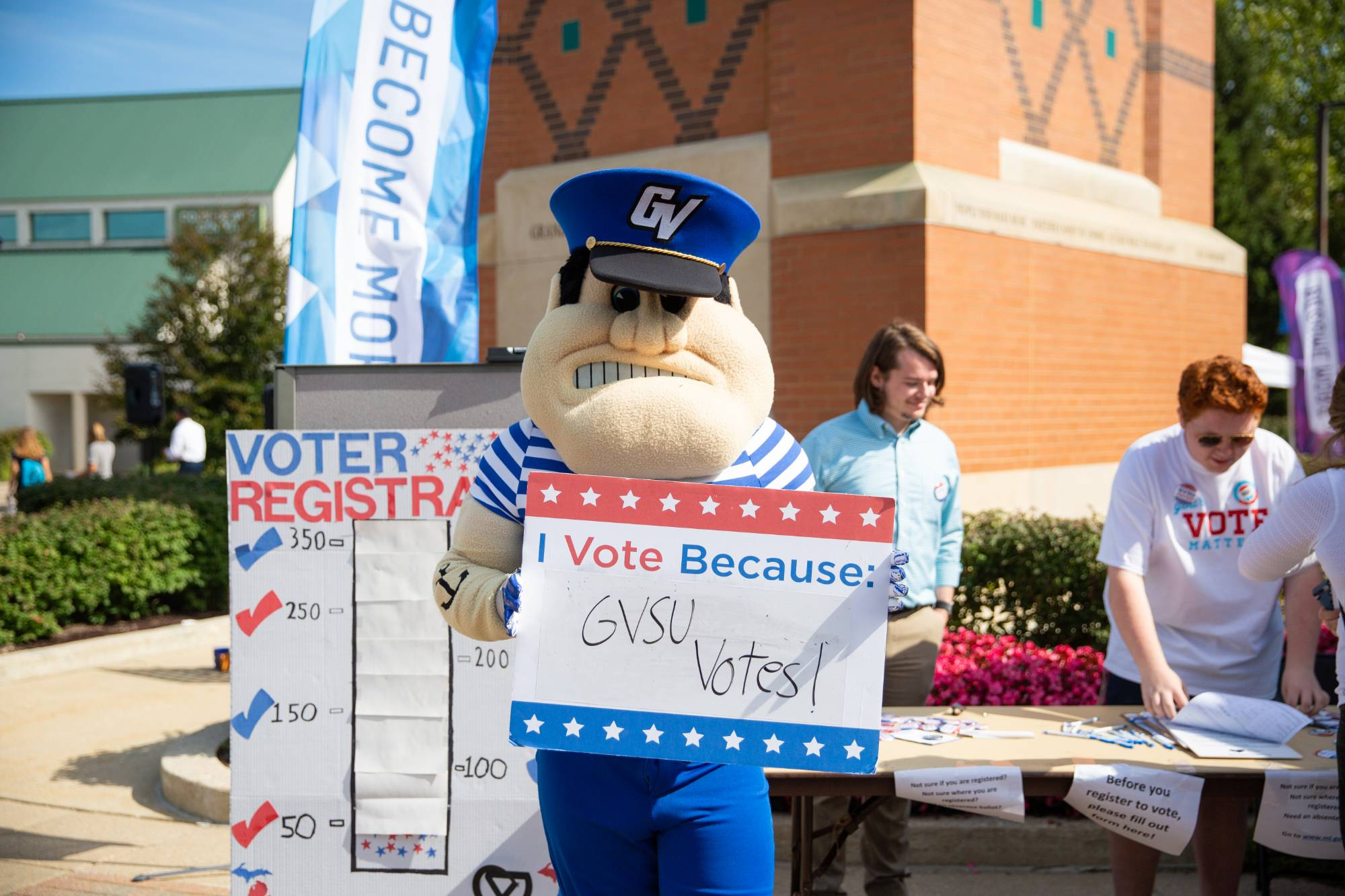 Louise the Laker holding a GVSU votes sing